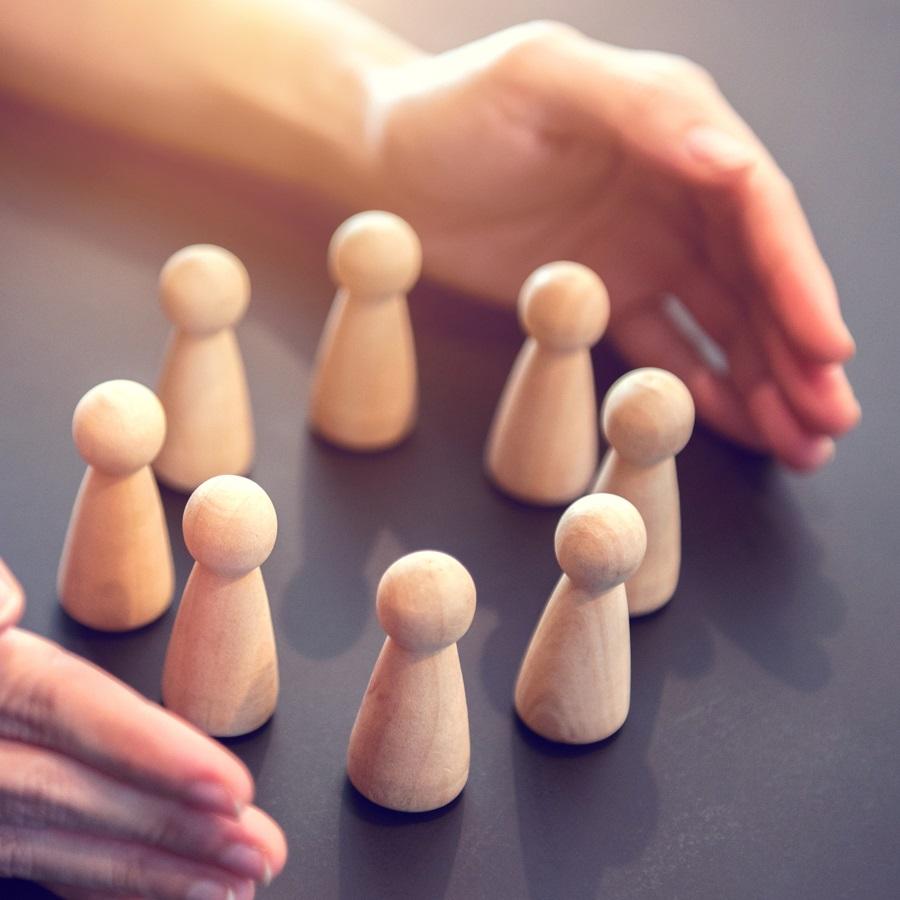 Picture of hands surrounding wooden stick figures