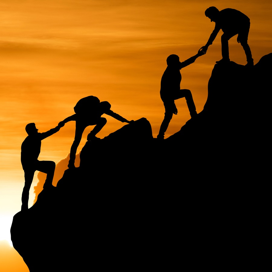 picture of people climbing a hill helping each other