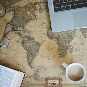 Picture of map with computer, coffee and book placed on it