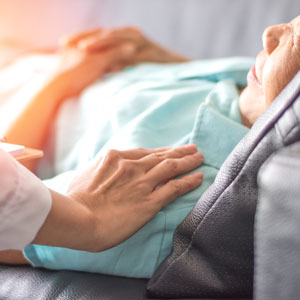 picture of hand comforting person laying in hospital bed