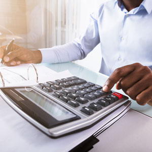 Picture of man at desk using a calculator