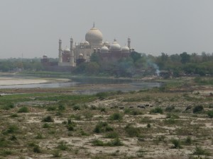 A cremation at the river's edge with Taj Mahal in background