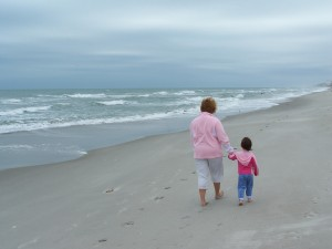 Picture of a mom walking on the beach with her daughter.