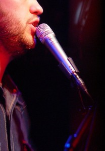 A man singing into a microphone with just his lips and chin visible