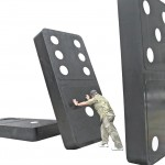 Man pushing over a huge domino