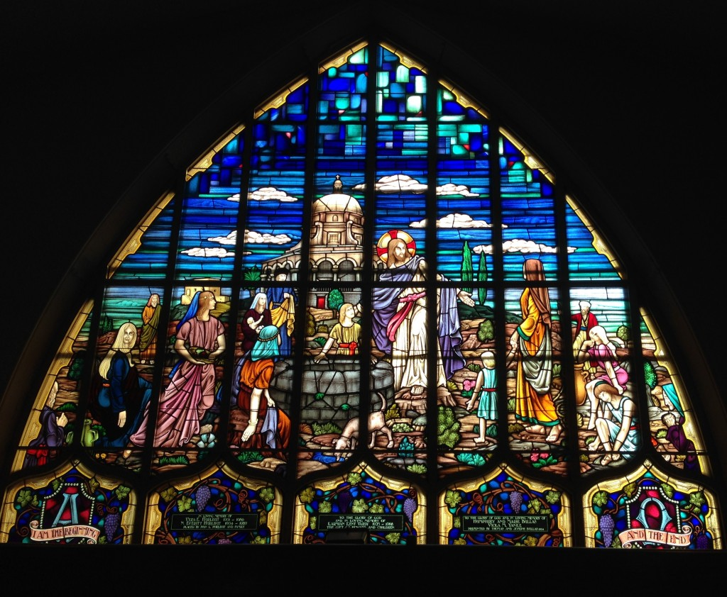 Stained Glass window of Jesus with people